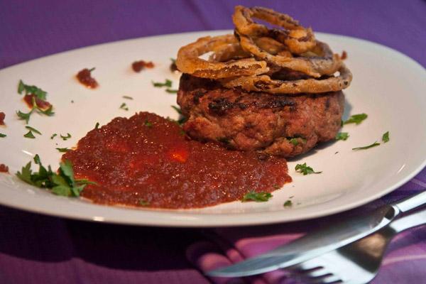 γκουρμέ μπέργκερ με πορτσίνι, τηγανητά δαχτυλίδια κρεμμυδιού και σάλτσα ντομάτας
