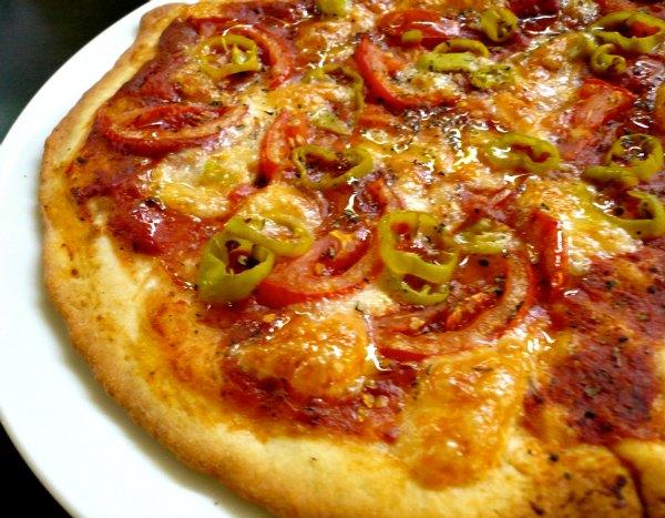 σπιτική πίτσα με ελαιόλαδο, φρέσκια ντομάτα, ρίγανη και πιπεριές