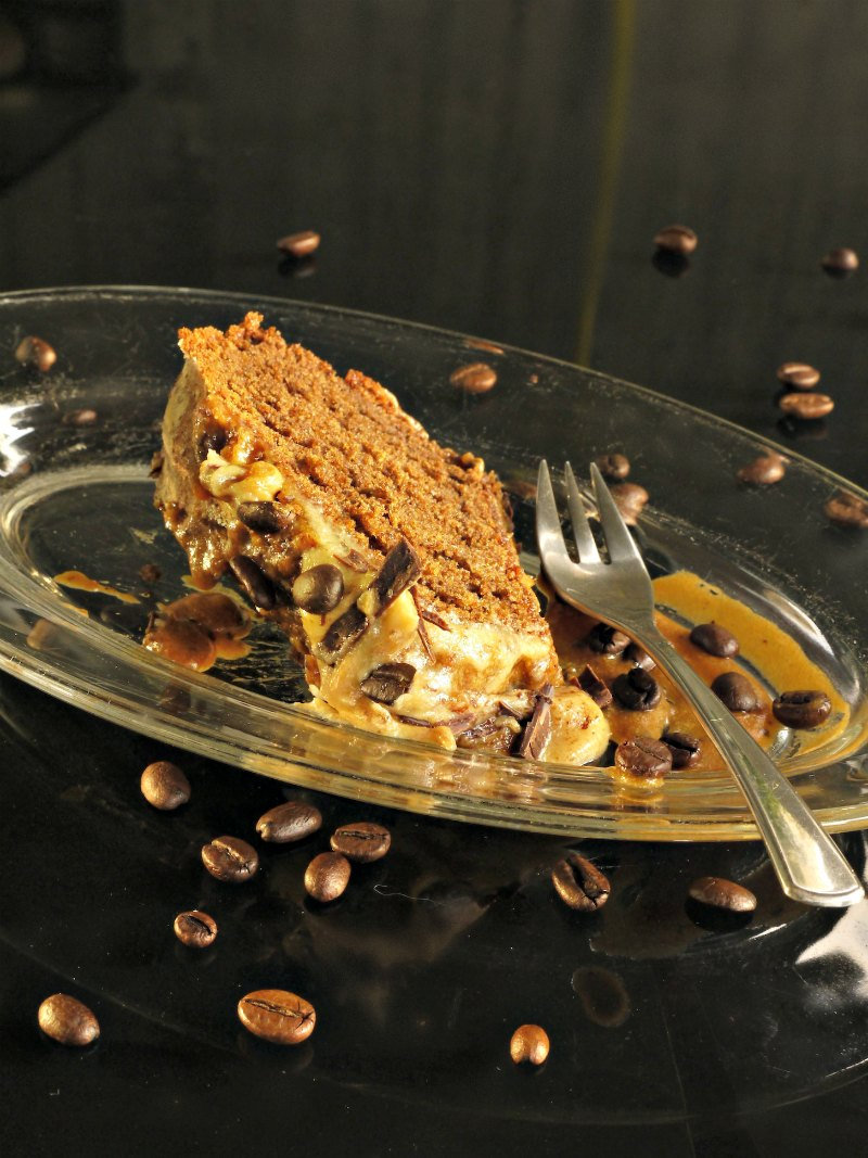A slice of the coffee flavoured cake with espresso frosting, chocolate slivers and coffee beans next to a fork on a plate