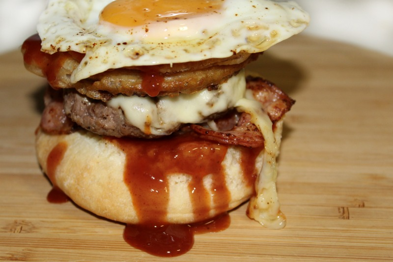 Homemade burger loaded with smoked bacon, onion rings, fried egg and smoky barbecue sauce