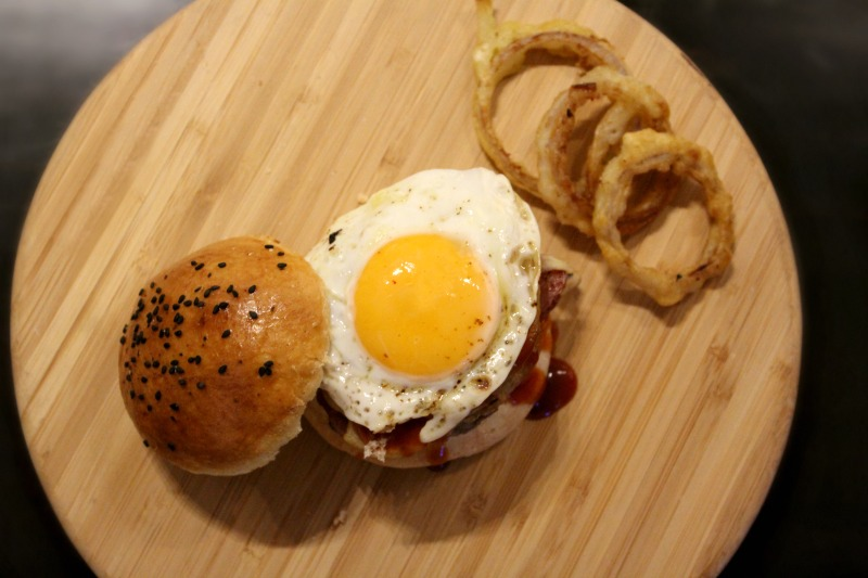 burger with smoked bacon, onion rings, fried egg and homemade barbecue sauce