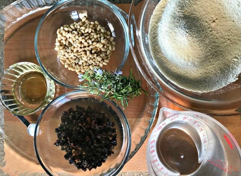 τα υλικά: καστανάλευρο, σταφίδες, ελαιόλαδο, κουκουνάρι, δενδρολίβανο