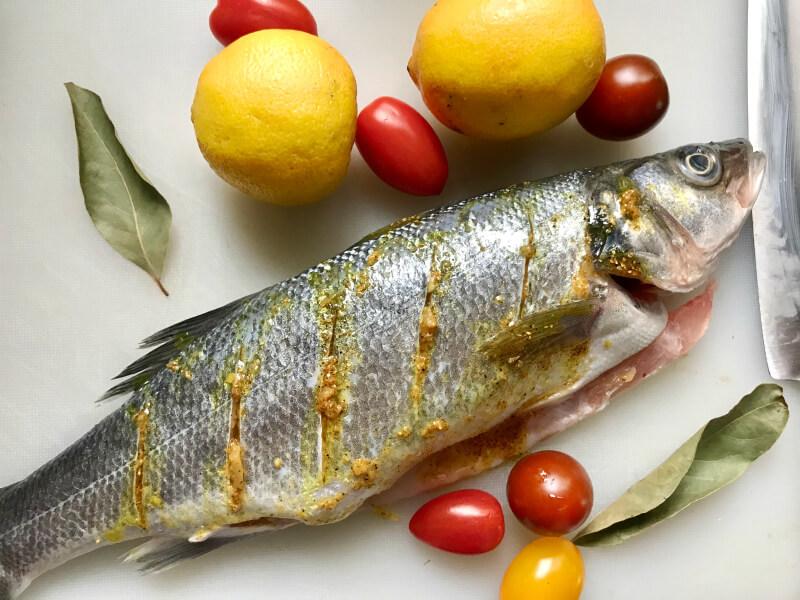 Ψάρι ολόκληρο, λαβράκι χαραγμένο, με αρωματισμένο με μπαχαρικά ελαιόλαδο, λεμόνια, δάφνη και ντοματίνια