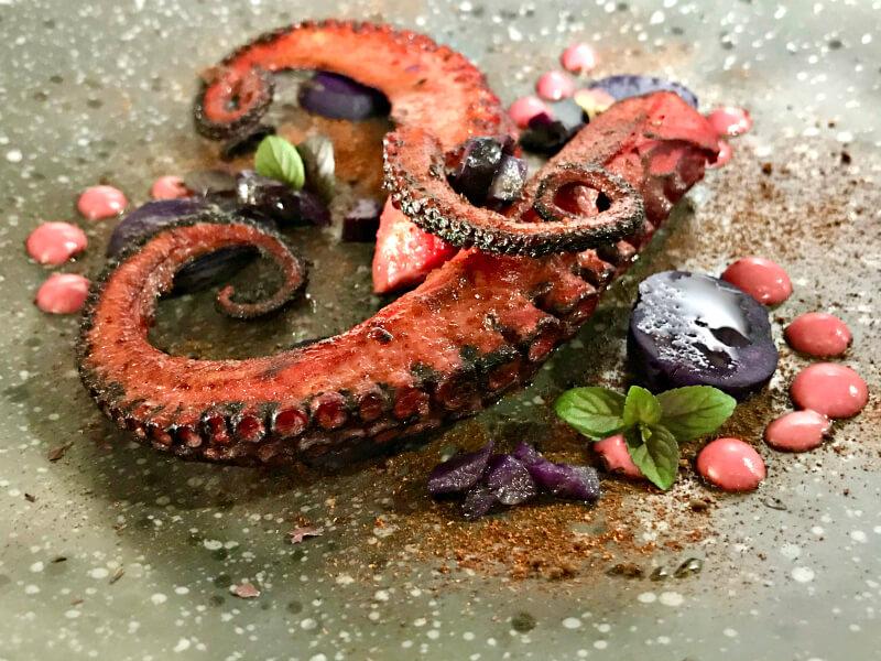 Βραστό και περασμένο στο τηγάνι χταπόδι με μοβ πατάτες