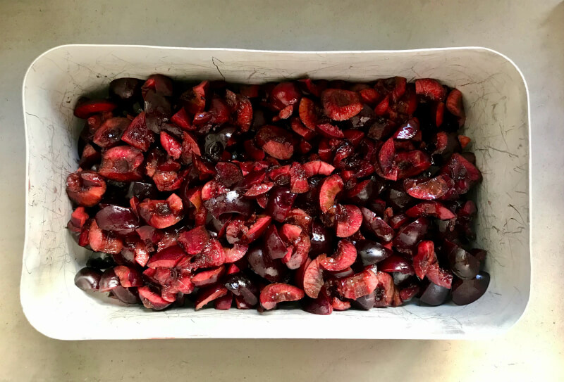 chopped cherries in container to freeze